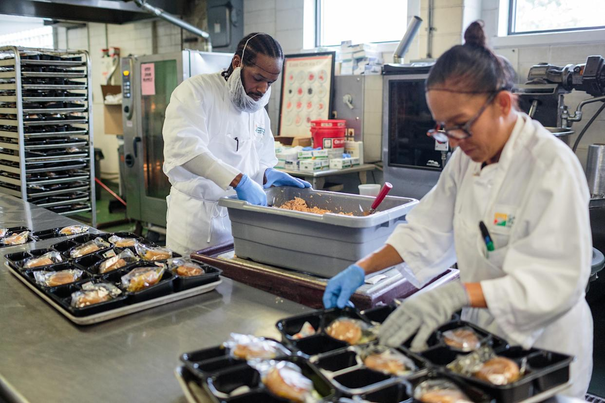 Caroline Torres, right, and Lamar Robinson prepare after-school meals at the Community Food Bank of New Jersey in Hillside, N.J., Oct. 30, 2019. (Sarah Blesener/The New York Times)