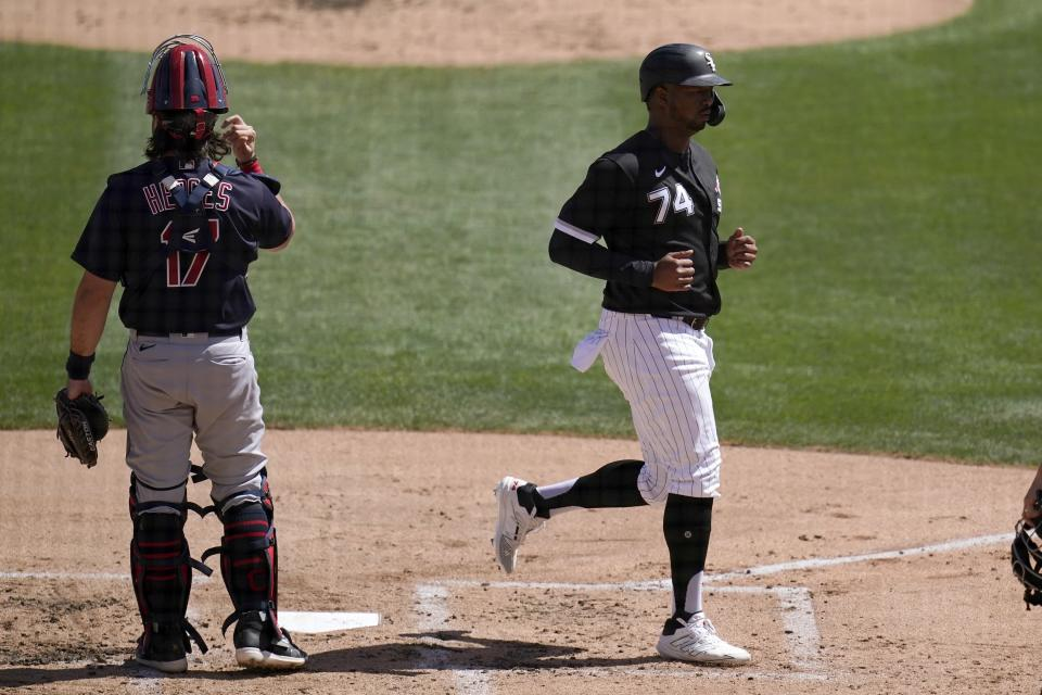 Chicago White Sox's Eloy Jimenez, right, scores a run as Cleveland Indians catcher Austin Hedges pauses at home plate during the first inning of a spring training baseball game Saturday, March 20, 2021, in Phoenix. (AP Photo/Ross D. Franklin)