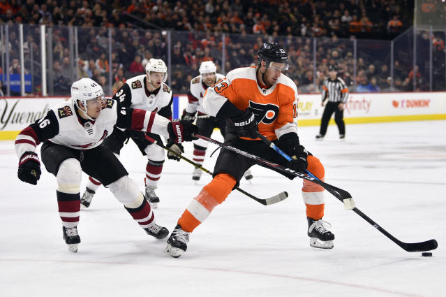 Philadelphia Flyers' Kevin Hayes, right, protects the puck from Arizona Coyotes' Ilya Lyubushkin during the second period of an NHL hockey game, Thursday, Dec. 5, 2019, in Philadelphia. (AP Photo/Derik Hamilton)