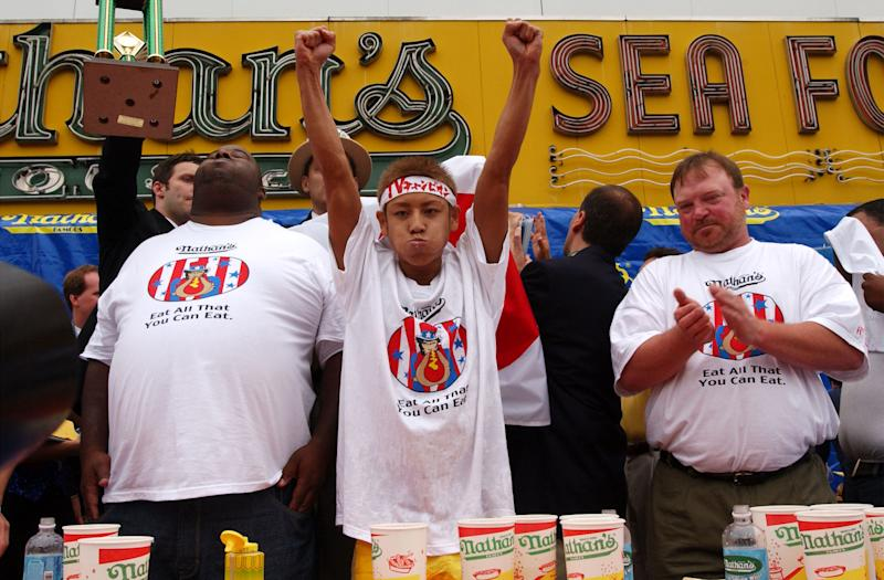 Contestants applaud as 23-year-old Takeru Kobayash raises his hands in victory July 4, 2001 at the 86th annual Nathan's Hot Dog Eating Contest at Coney Island in Brooklyn, New York.