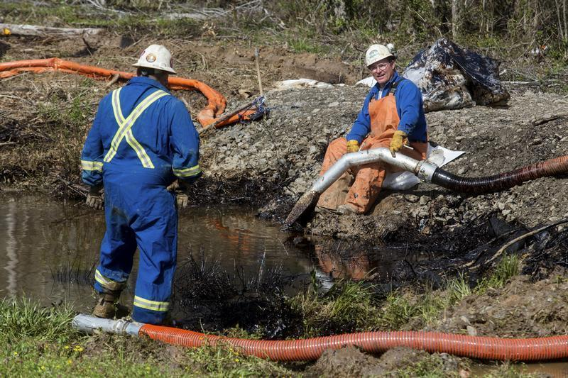 Emergency crews work to clean up an oil spill near Interstate 40 in Mayflower