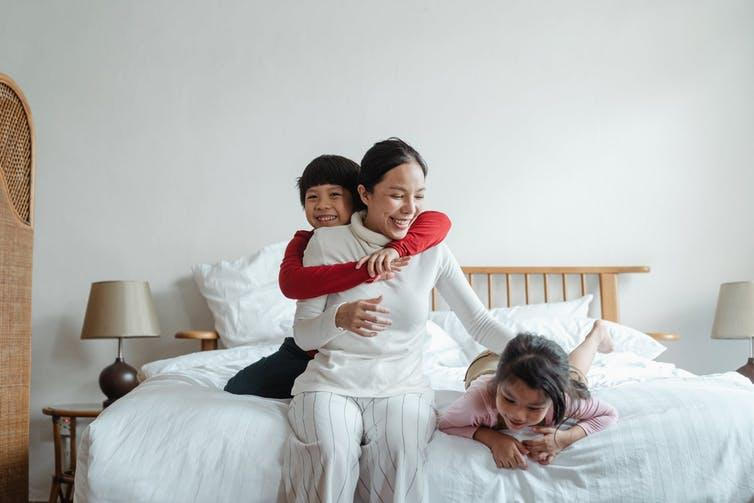 Cheerful mother playing with and hugging her children on the bed.