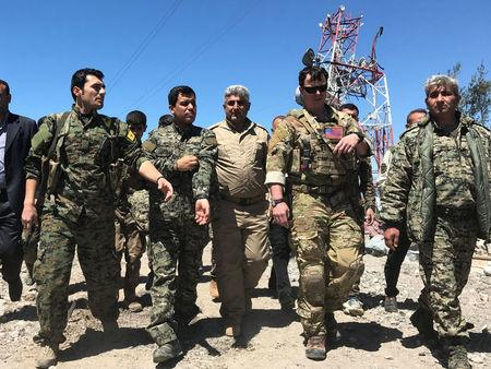 A U.S. military commander (2nd R) walks with Kurdish fighters from the People's Protection Units (YPG) at the YPG headquarters that was hit by Turkish airstrikes in Mount Karachok near Malikiya, Syria April 25, 2017. REUTERS/Rodi Said