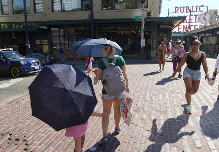 A woman and her daughter carry umbrellas while walking through Seattle's Public Market.