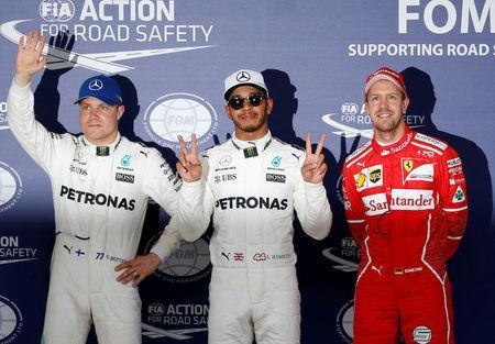 Mercedes' Lewis Hamilton of Britain celebrates pole position in qualifying with Valtteri Bottas of Finland and Ferrari's Sebastian Vettel of Germany. REUTERS/Toru Hanai