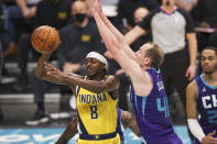 Indiana Pacers guard Justin Holiday (8) passes the ball while Charlotte Hornets center Cody Zeller (40) defends during the first half of an NBA basketball game in Charlotte, N.C., Wednesday, Jan. 27, 2021. (AP Photo/Nell Redmond)