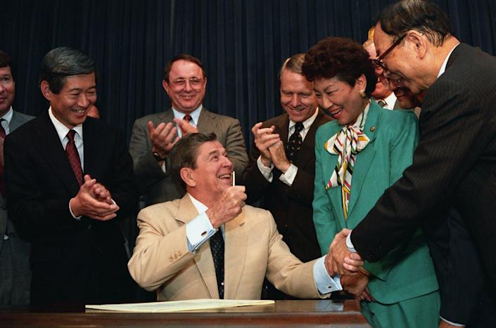 Ronald Reagan, sitting, shakes hands with smiling people
