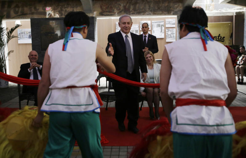 Israeli Prime Minister Benjamin Netanyahu, center, reaches out to shake hands with Chinese traditional lion dance performers as he visits Shanghai Jewish Refugees Museum at former site of Ohel Moshe Synagogue in Shanghai, China, Tuesday, May 7, 2013. China is hosting both the Palestinian and Israeli leaders this week in a sign of its desire for a larger role in the Middle East. Seated behind Netanyahu is his wife, Sara. (AP Photo/Eugene Hoshiko)