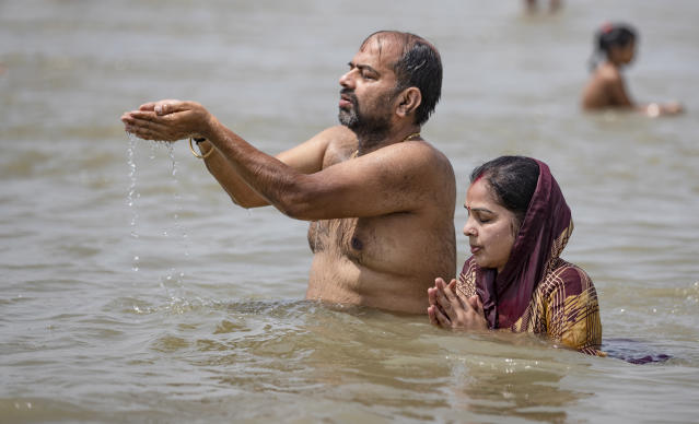 Hindu devotees offer prayers in the River Ganges, during the Ganga Dussehra festival, in Prayagraj, India, Monday, June 1, 2020. Hundreds of Hindu devotees made holy dips here Monday even though congregations at religious venues continue to remain barred during the nationwide coronavirus lockdown. (AP Photo/Rajesh Kumar Singh)
