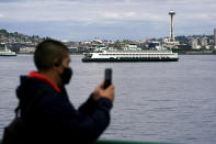 File-In this May 25, 2021 file photo a passenger wears a mask while riding on a Washington state ferry from Bremerton to Seattle as another ferry passes near the Space Needle, in Seattle. Washington and Oregon, which were among the first states to impose broad COVID-19 restrictions, on Wednesday, June 30, 201, lifted most rules to become among the last states to broadly ease pandemic orders put in place more than a year ago. (AP Photo/Ted S. Warren,File)