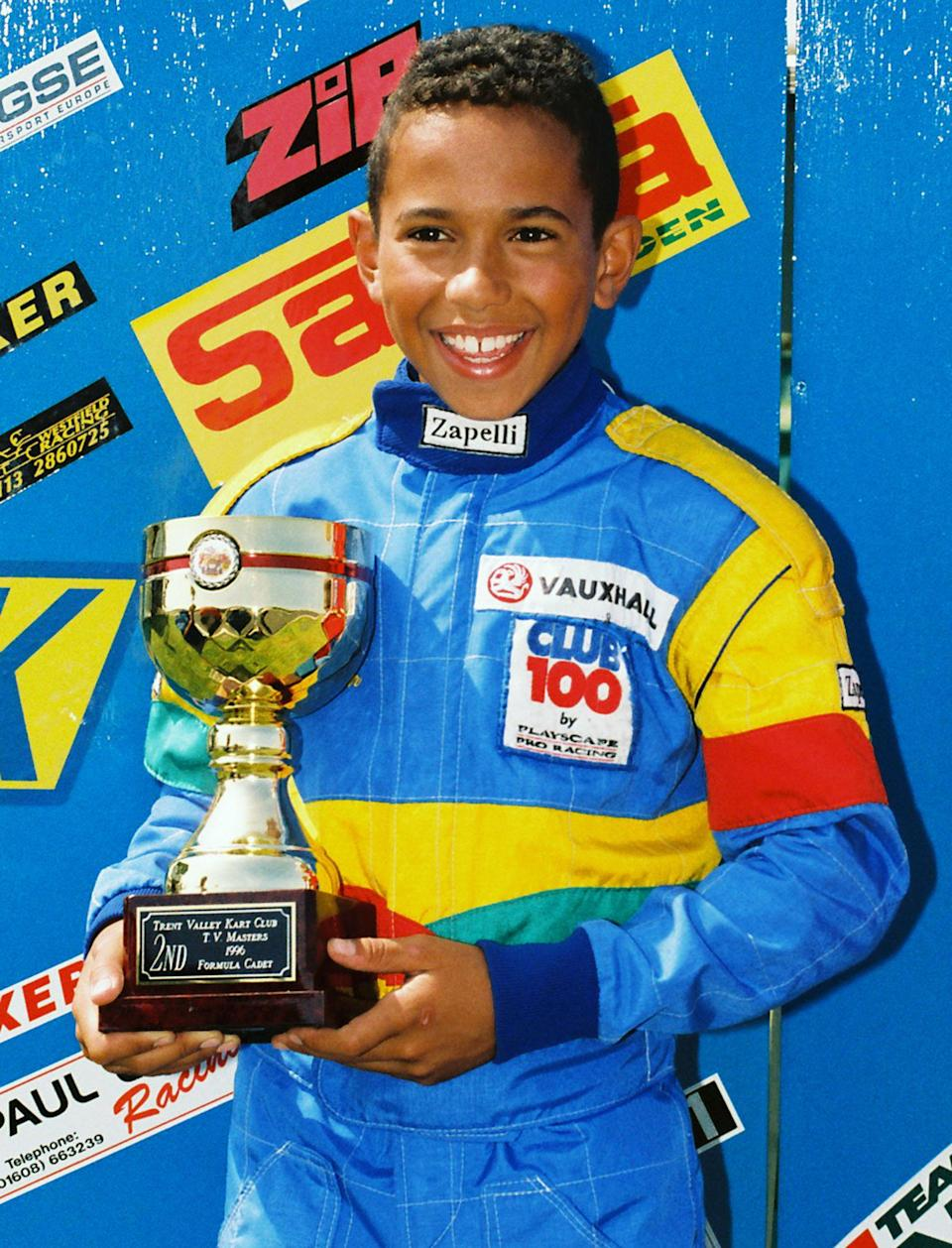 Little boy blue: Lewis Hamilton picks up a Formula Cadet trophy in 1996 – and he's smiling, even though he came second