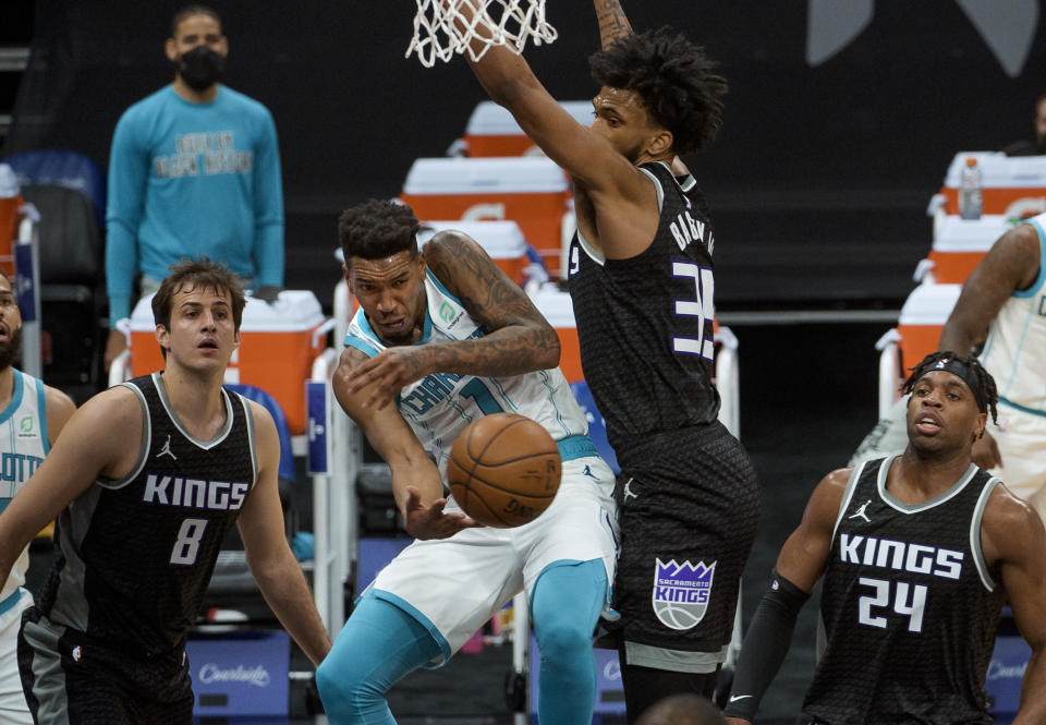 Charlotte Hornets guard Malik Monk (1)passes the ball around Sacramento Kings forward Marvin Bagley III (35) during the first quarter of an NBA basketball game in Sacramento, Calif., Sunday, Feb. 28, 2021. (AP Photo/Randall Benton)