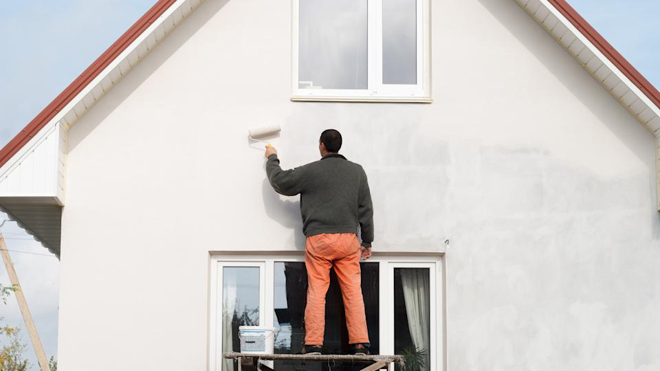 construction worker is painting a wall with a roller.