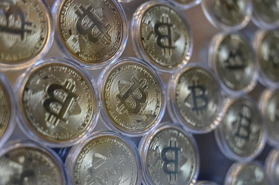 """This photograph taken on December 17, 2020 shows shows a physical imitation of a Bitcoin at a crypto currency """"Bitcoin Change"""" shop, near Grand Bazaar, in Istanbul. - Leading virtual currency bitcoin on 16 December traded above $20,000 for the first time following a sustained run higher in recent weeks. Bitcoin reached a record-high $20,398.50 before pulling back to $20,145, which was still an intra-day gain of nearly four percent. (Photo by Ozan KOSE / AFP) (Photo by OZAN KOSE/AFP via Getty Images)"""