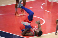 Philadelphia 76ers center Joel Embiid (21) grabs his knee after he was injured during the second half of the team's NBA basketball game against the Washington Wizards, Friday, March 12, 2021, in Washington. (AP Photo/Nick Wass)