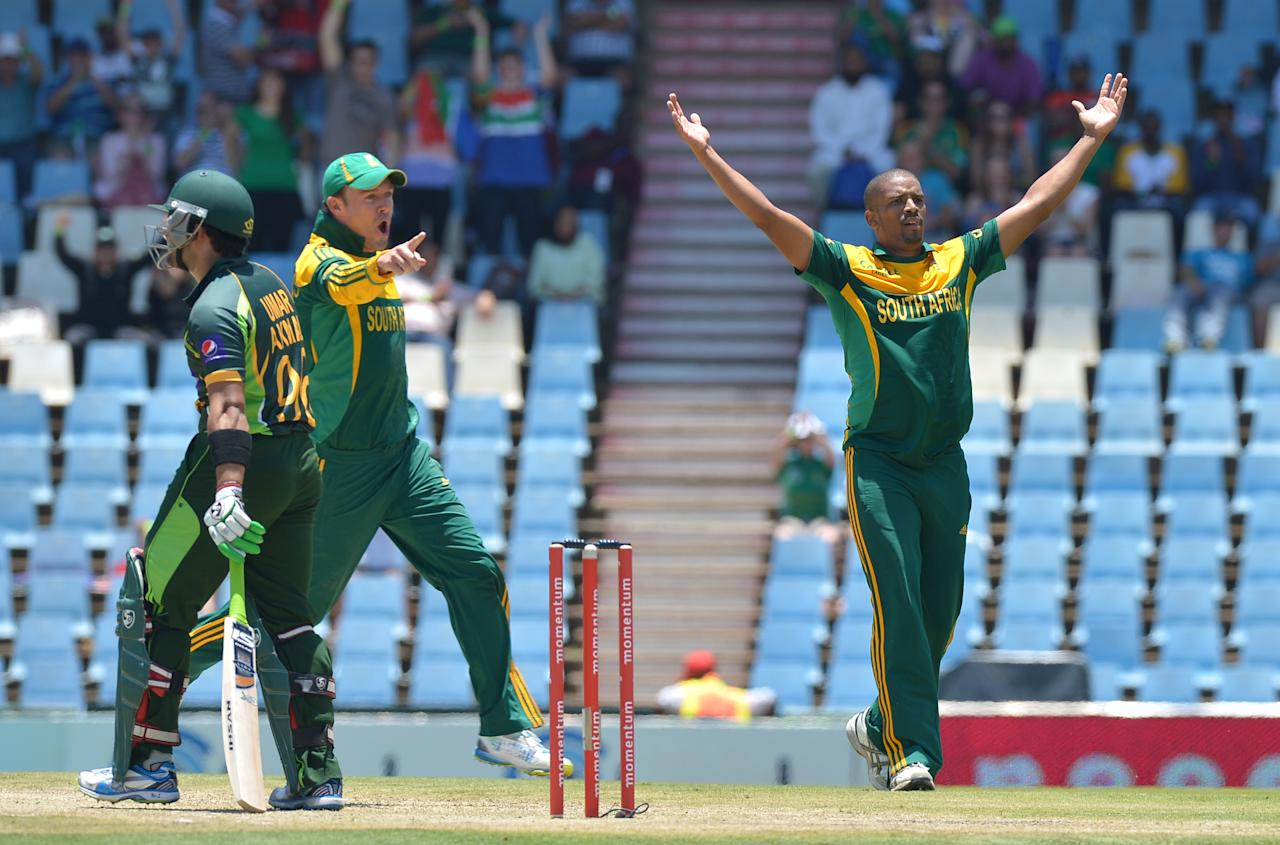 South Africa's cricketer Vernon Philander (R) celebrates the wicket of Pakistan's cricketer Umar Akmal, during the final ODI between South Africa and Pakistan at SuperSport Park in Centurion on November 30, 2013.  AFP PHOTO / ALEXANDER JOE