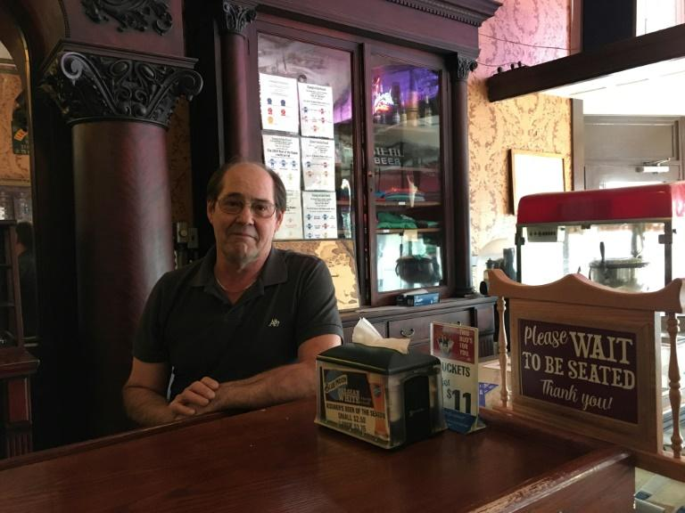 Karl Kissner, the third-generation owner of a diner bearing his family's name in Defiance, Ohio, serves customers at the bar, with Fox News on the television showing President Donald Trump's impeachment trial (AFP Photo/Shaun TANDON)