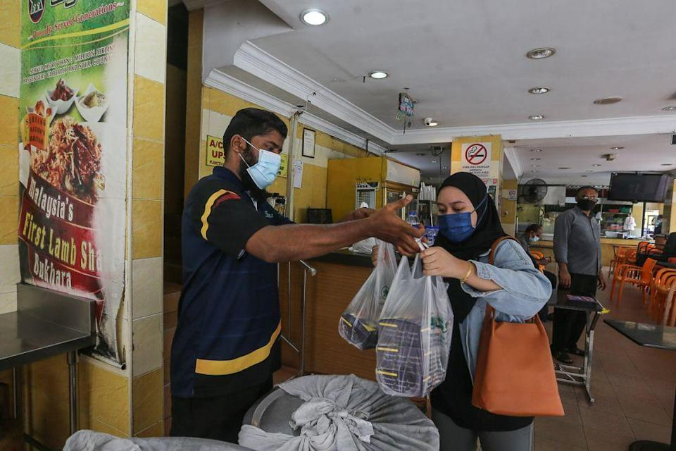 A patron packs food to go at Syed Bistro Restaurant in Puchong June 14, 2021. — Picture by Yusof Mat Isa