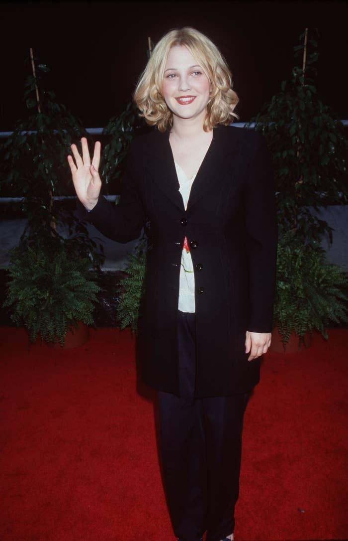 Drew Barrymore waves on the red carpet while wearing a buttoned shirt, blouse, and pants.