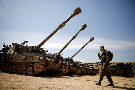 An Israeli soldier walks next to a battery of cannons  near the border with Gaza, in southern Israel