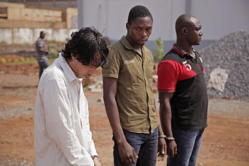 A Vietnamese man, left, and his two Togolese accomplices are paraded by Togo troops to the media in the city of Lome, Togo, Tuesday, Jan. 28, 2014. Police in Togo say they have arrested three men after discovering nearly two tons of ivory in a container marked for shipping to Vietnam. (AP Photo/Erick Kaglan)