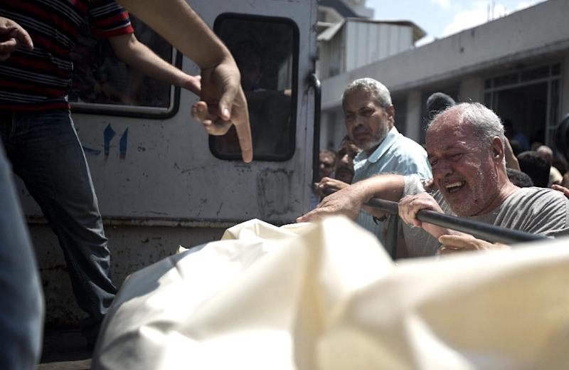A Palestinian man from Halaq family grives over the body of a relative outside the mourgue of the al-Shifa hospital, in Gaza City, on July 21, 2014