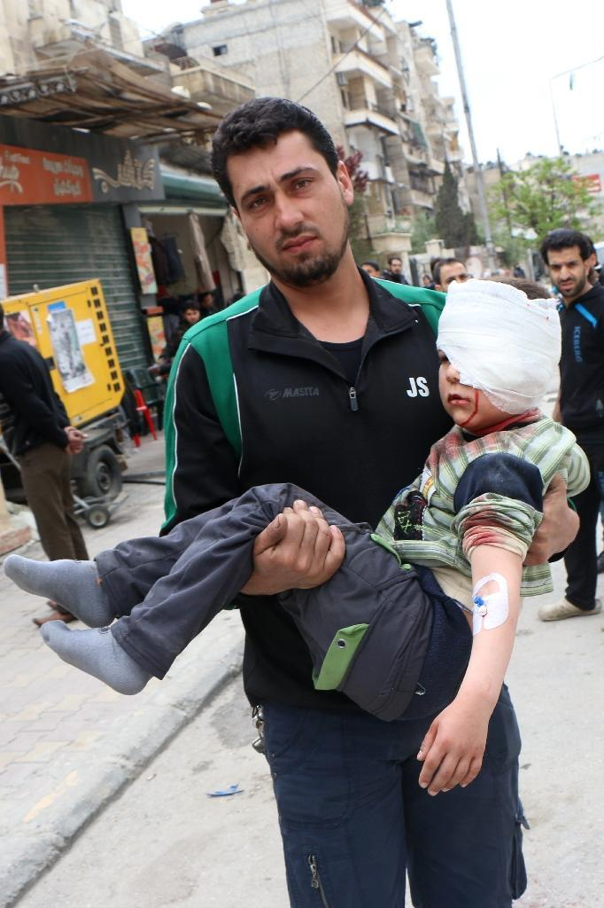 A Syrian man carries an injured child in the northern city of Aleppo on April 12, 2015, following a reported Syrian regime air strike on Saad Ansari school that killed five children and four other civilians (AFP Photo/Zein Al-Rifai)