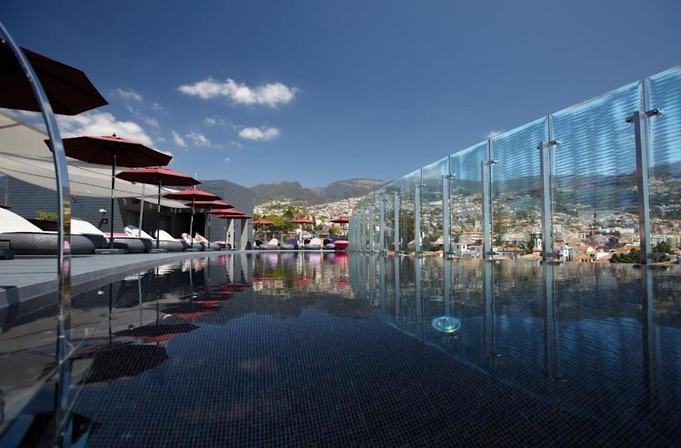 """<p>Right in the heart of Funchal – and with a rooftop pool that looks out across the bay – this ultra-modern luxury hotel draws design inspiration from Madeira's world-class reputation for wine-making. </p><p>At <a href=""""https://go.redirectingat.com?id=127X1599956&url=https%3A%2F%2Fwww.booking.com%2Fhotel%2Fpt%2Fthe-vine.en-gb.html%3Faid%3D1922306%26label%3Dmadeira-hotels&sref=https%3A%2F%2Fwww.goodhousekeeping.com%2Fuk%2Flifestyle%2Ftravel%2Fg37065833%2Fmadeira-hotels%2F"""" rel=""""nofollow noopener"""" target=""""_blank"""" data-ylk=""""slk:The Vine"""" class=""""link rapid-noclick-resp"""">The Vine</a>, So The Terrace restaurant's romantic outdoor space is surrounded by vines, with chic furniture that copies the twisting branches, while at Uva (Portuguese for grape) up on the roof, you can drink and dine with magical views. The theme continues in the spa, where you can enjoy treatments like a crushed grape seed body scrub or an antioxidant red wine bath.</p><a class=""""link rapid-noclick-resp"""" href=""""https://go.redirectingat.com?id=127X1599956&url=https%3A%2F%2Fwww.booking.com%2Fhotel%2Fpt%2Fthe-vine.en-gb.html%3Faid%3D1922306%26label%3Dmadeira-hotels&sref=https%3A%2F%2Fwww.goodhousekeeping.com%2Fuk%2Flifestyle%2Ftravel%2Fg37065833%2Fmadeira-hotels%2F"""" rel=""""nofollow noopener"""" target=""""_blank"""" data-ylk=""""slk:CHECK AVAILABILITY"""">CHECK AVAILABILITY</a>"""