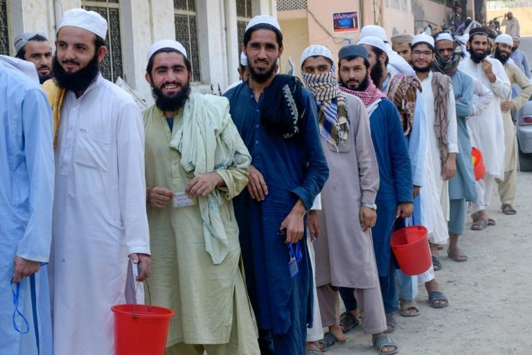 Students wait to collect food at the Darul Uloom Haqqania seminary