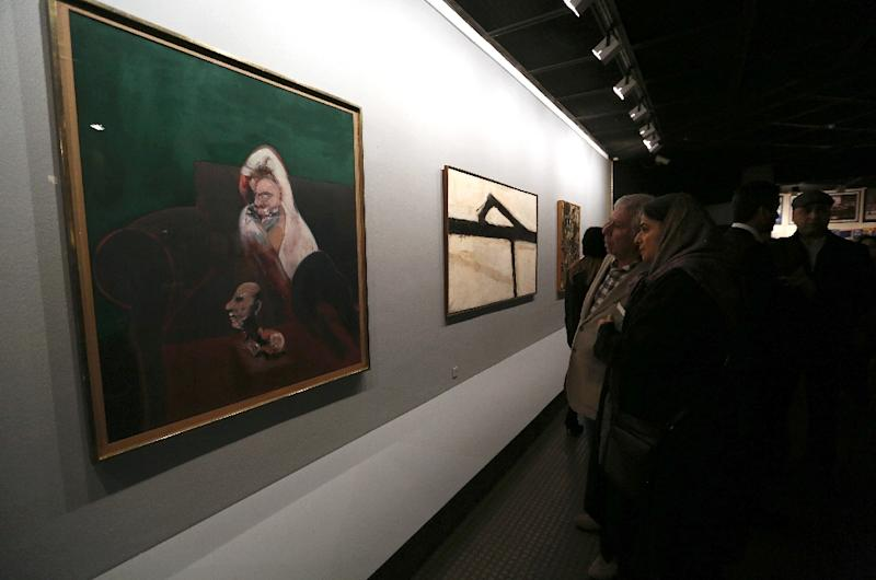 """Visitors take in Irish-born British painter Francis Bacon's """"Reclining Man with Sculpture"""" (L) and American artist Franz Kline's """"Untitled"""" in Tehran on November 20, 2015 (AFP Photo/Atta Kenare)"""