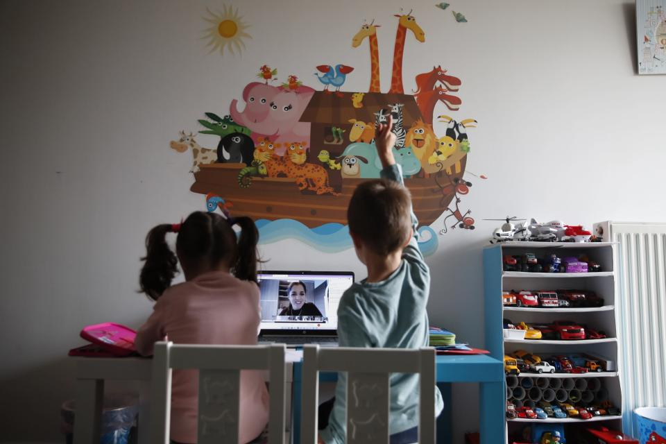 A kindergarten teacher reads a fairy story as Panos raising his hand with his twin sister Marina watch the online lesson in Athens, Thursday, Nov. 19, 2020. Most other European countries have vowed to keep schools open, but the pandemic has hit Greece hard for the first time in recent weeks following a successful lockdown in the spring, overwhelming hospitals in parts of the country. State television is making and broadcasting lessons, while teachers sit in empty classrooms talking to remote students. Despite some problems, they say it keeps children in touch with their schools. (AP Photo/Thanassis Stavrakis)