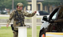A military policeman turns away traffic at JBSA-Lackland Air Force Base game, Wednesday, June 9, 2021, in San Antonio. The Air Force was put on lockdown as police and military officials say they searched for two people suspected of shooting into the base from outside. (AP Photo/Eric Gay)