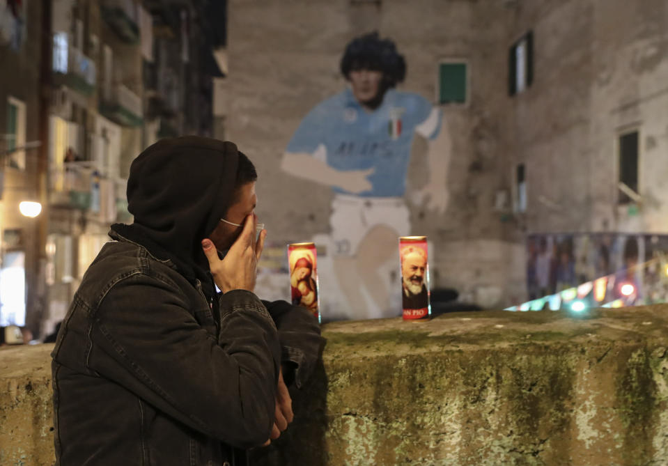 A man cries under a mural depicting soccer legend Diego Maradona, in Naples, Italy, Wednesday, Nov. 25, 2020. Diego Maradona has died. The Argentine soccer great was among the best players ever and who led his country to the 1986 World Cup title before later struggling with cocaine use and obesity. He was 60. (AP Photo/Salvatore Laporta)