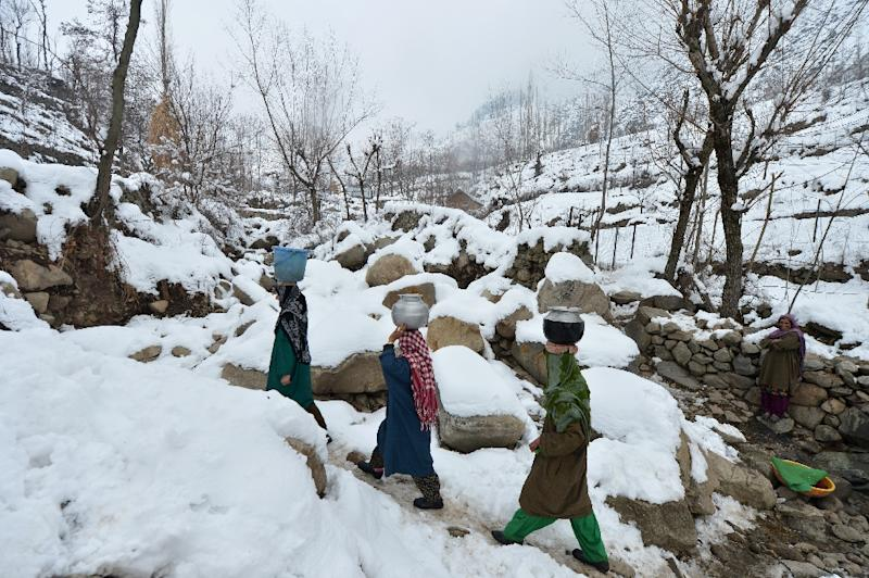 Villagers carry drinking water on the outskirts of Srinagar