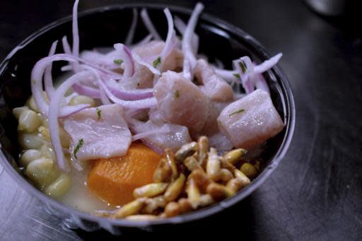 In this Aug. 8, 2019 photo, a Peruvian ceviche is ready for a costumer at the international center outside the Pan American athletes' village in Lima, Peru. Peruvian food was the star at the recent Pan Am Games held in Latin Americas culinary capital. Athletes from countries across the Americas tasted the highly-regarded cuisine that blends indigenous traditions with European, African and Asian influences with an abundance of seafood from the Pacific Oceans cold Humboldt current. (AP Photo/Luis Andres Henao)