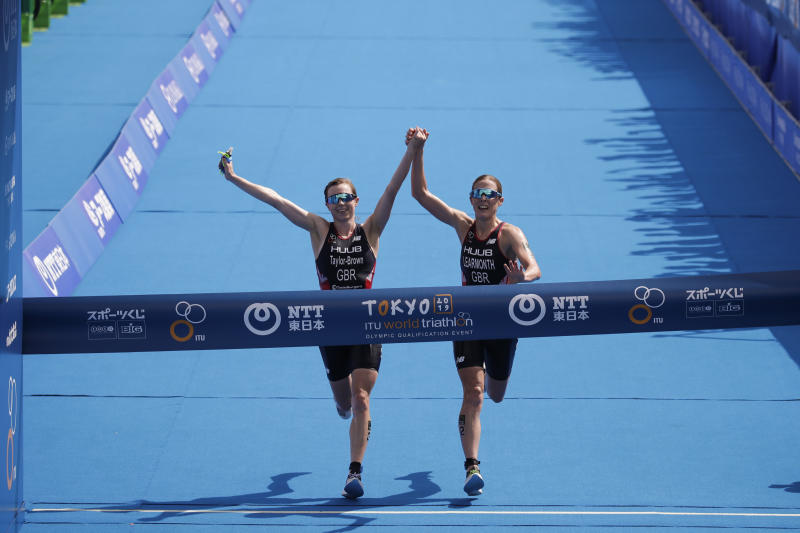 Britain's Georgia Taylor-Brown, left, and Jessica Learmonth hold hands as they cross the finish line during a women's triathlon test event at Odaiba Marine Park, a venue for marathon swimming and triathlon at the Tokyo 2020 Olympics, Thursday, Aug. 15, 2019, in Tokyo. (AP Photo/Jae C. Hong)