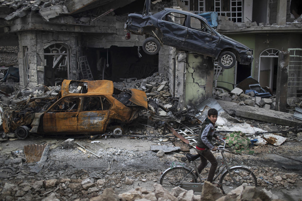 <p>A boy rides his bike past destroyed cars and houses in a neighborhood recently liberated by Iraqi security forces, on the western side of Mosul, Iraq, March 19, 2017. (Photo: Felipe Dana/AP) </p>