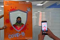 A woman has her photograph taken after getting inoculated in Mumbai
