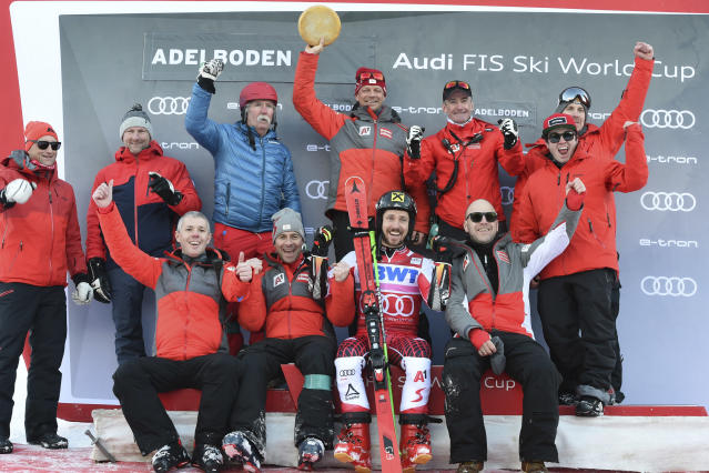 First placed Austria's Marcel Hirscher, sitting second from right, celebrates with teammates at the end of a ski World Cup men's Giant Slalom in Adelboden, Switzerland, Saturday, Jan. 12, 2019. (AP Photo/Marco Tacca)