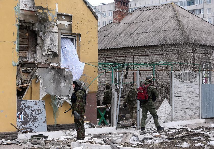 Ukrainian servicemen patrol around a damaged building after shelling in the southern Ukrainian port city of Mariupol on January 24, 2015 (AFP Photo/)