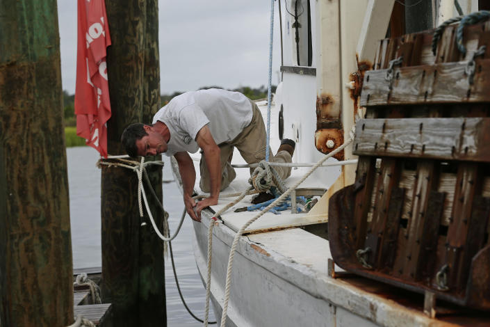 Royce Potter, a fifth generation seafood farmer, suveys the damage to his fishing vessel following the effects of Hurricane Isaias in Southport, N.C., Tuesday, Aug. 4, 2020. Potter spent the night on his docked boat. (AP Photo/Gerry Broome)