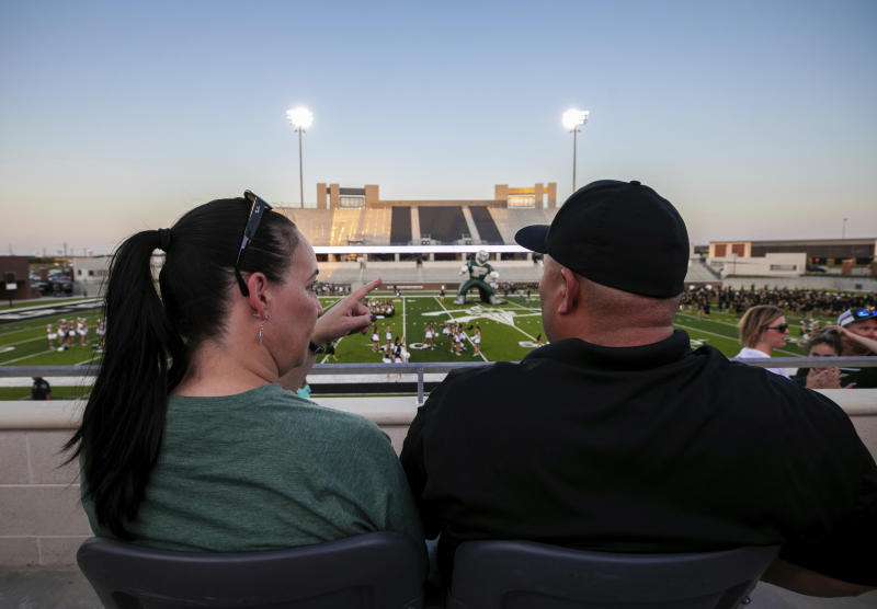 Lisa DeMarco and Rey Martinez watch students on the field during the opening of the new Children's Health Stadium at Prosper ISD on Saturday, Aug. 17, 2019, in Prosper, Texas. Democrats are out to show they're serious about flipping Texas in 2020 by holding Thursday's presidential debate in Houston. Republicans are coming off their worst election in Texas in a generation. Fast-changing suburbs are trending more liberal, and Democrats are counting on more left-leaning voters moving in to turn the state blue. But that transformation may not arrive by 2020, and the GOP is closely watching conservative bastions like the booming Dallas suburbs. (AP Photo/Nathan Hunsinger)