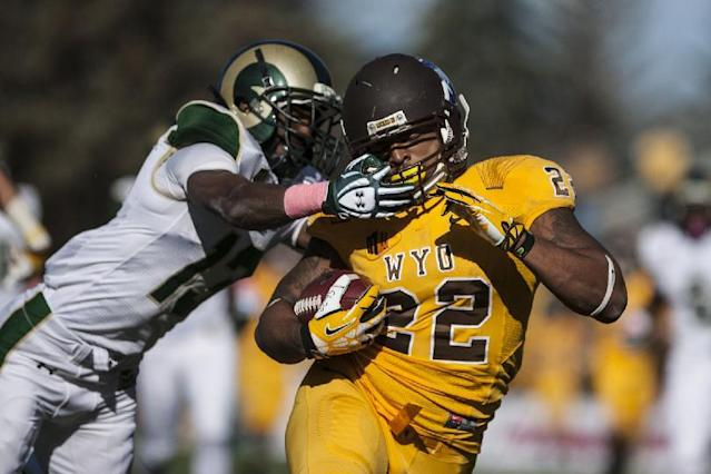 Wyoming's Tedder Easton is grabbed by Colorado State's DeAndre Elliott while running in a touchdown late in the second half of an NCAA college football game Saturday, Oct. 19, 2013, at War Memorial Stadium in Laramie, Wyo. (AP Photo/Casper Star-Tribune, Ryan Dorgan)