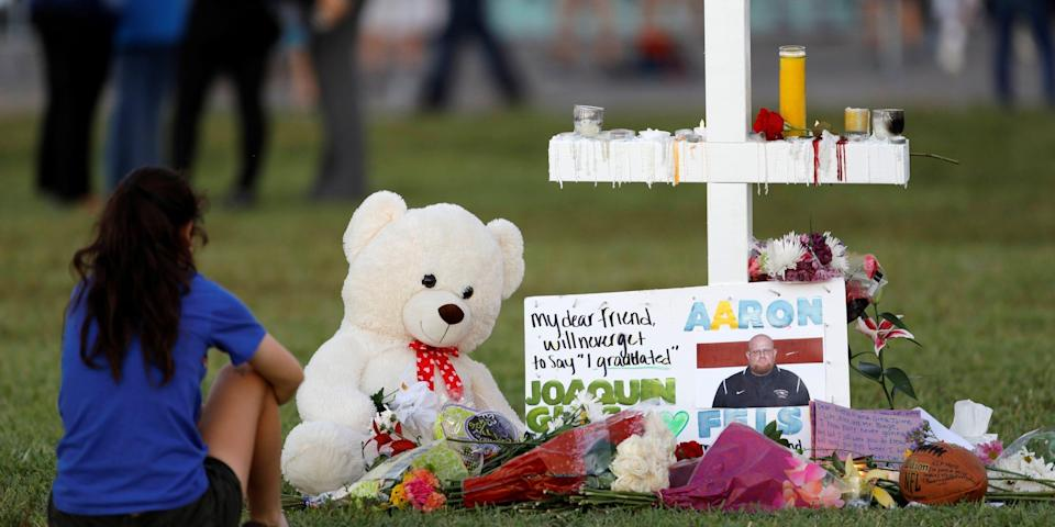 A mourner sits by a cross adorned with pictures of victims, along with flowers and other mementoes, at a memorial two days after the shooting at Marjory Stoneman Douglas High School in Parkland, Florida, U.S. February 16, 2018.