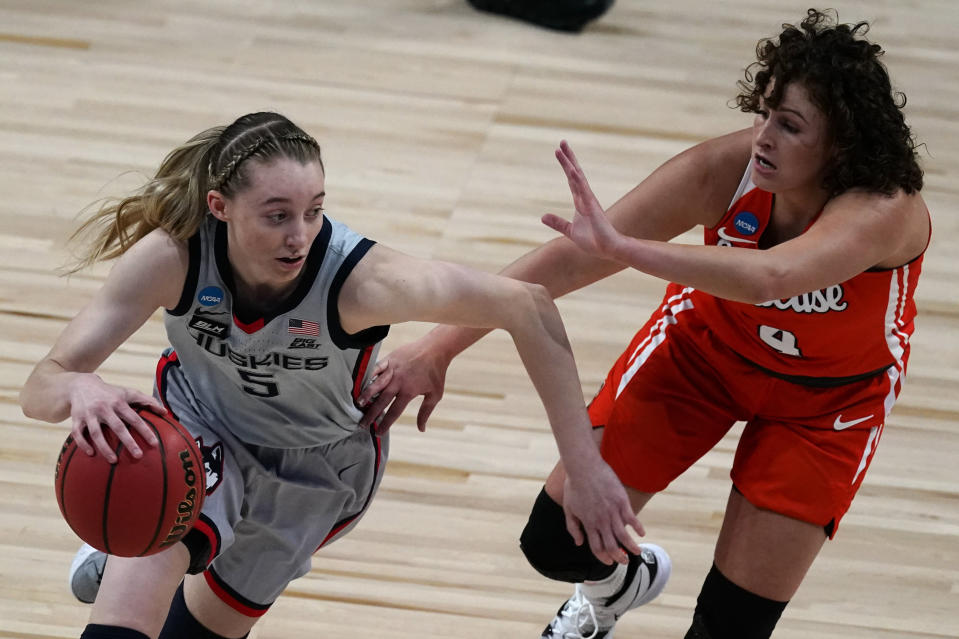 UConn guard Paige Bueckers (5) drives under pressure from Syracuse guard Tiana Mangakahia (4) during the first half of a college basketball game in the second round of the women's NCAA tournament at the Alamodome in San Antonio, Tuesday, March 23, 2021. (AP Photo/Charlie Riedel)