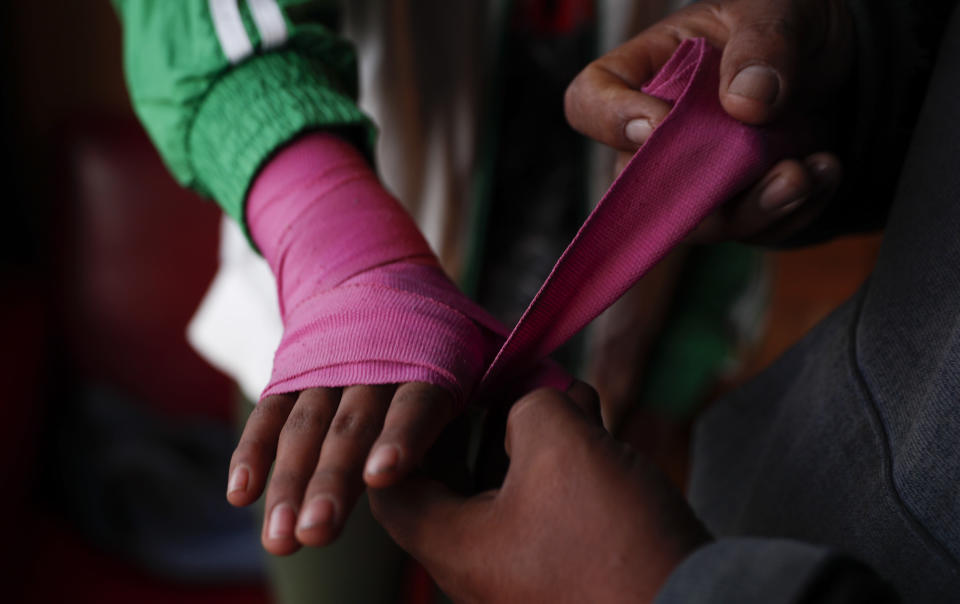Gracce Kelly Flores is helped by her father to put bandages on her hand before starting his boxing training in Palca, Bolivia, Thursday, June 10, 2021. (AP Photo/Juan Karita)
