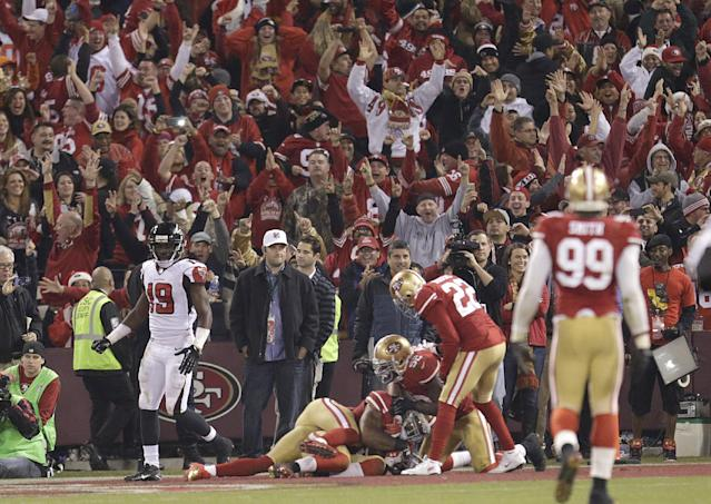 Fans celebrate after San Francisco 49ers linebacker NaVorro Bowman, bottom, returned an interception 89 yards for a touchdown during the fourth quarter of an NFL football game against the Atlanta Falcons in San Francisco, Monday, Dec. 23, 2013. The 49ers won 34-24. (AP Photo/Tony Avelar)
