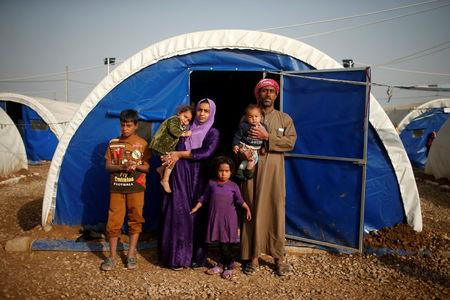 Displaced Iraqi Abdullah Mustafa, 38, poses for a photograph with his family at Hammam al-Alil camp south of Mosul, Iraq, March 29, 2017. Mustafa, a construction worker, says the family house was shelled in a mortar attack while they were inside but fortunately no one was hurt. Two days later, they fled their home. REUTERS/Suhaib Salem