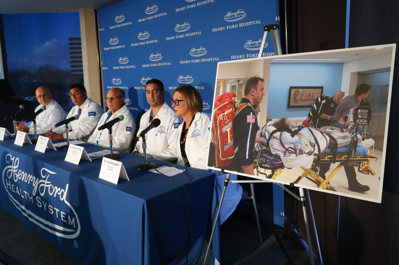 A photo of a patient being transported is displayed while medical staff at Henry Ford Hospital answer questions during a news conference in Detroit, Tuesday, Nov. 12, 2019. A Henry Ford Health System medical team performed a double lung transplant, for the unidentified patient in the photograph, whose lungs were irreparably damaged from vaping. (AP Photo/Paul Sancya)