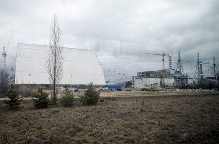 A general view shows a containment shelter for the damaged fourth reactor (R) and the New Safe Confinement (NSC) structure (L) at the Chernobyl Nuclear Power Plant, Ukraine, March 23, 2016. Picture taken through a window. REUTERS/Gleb Garanich